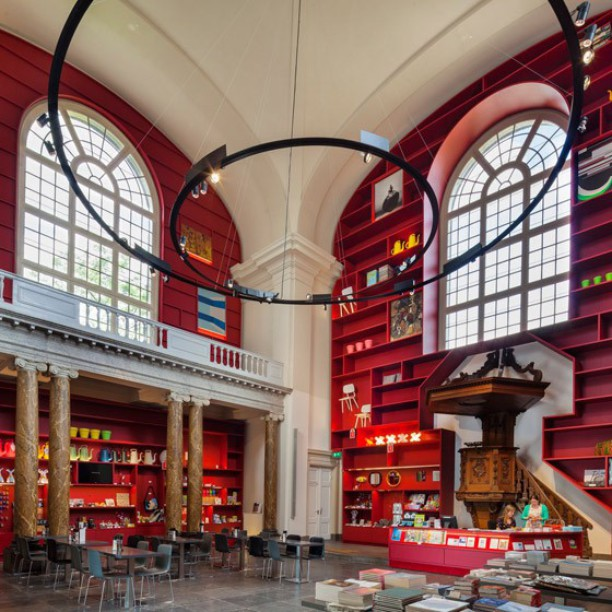 Dutch design studio MVRDV has transformed a neoclassical chapel into the main entrance for a MoMA in Schiedam, the Netherlands, adding bright red shelves between the listed building's existing features. #designinspiration #architecture #checkoutthosechairs